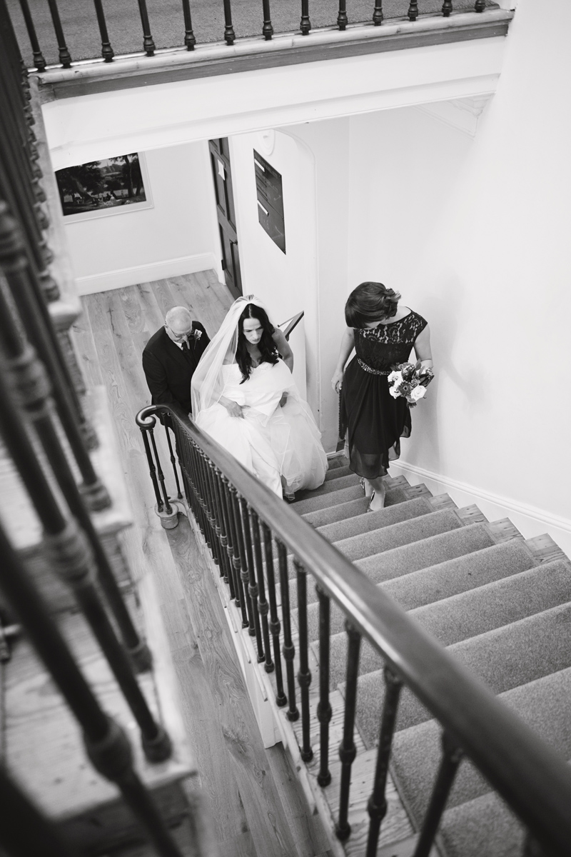 A bride walking up the stairs with her bridesmaid and father as they arrive at her wedding