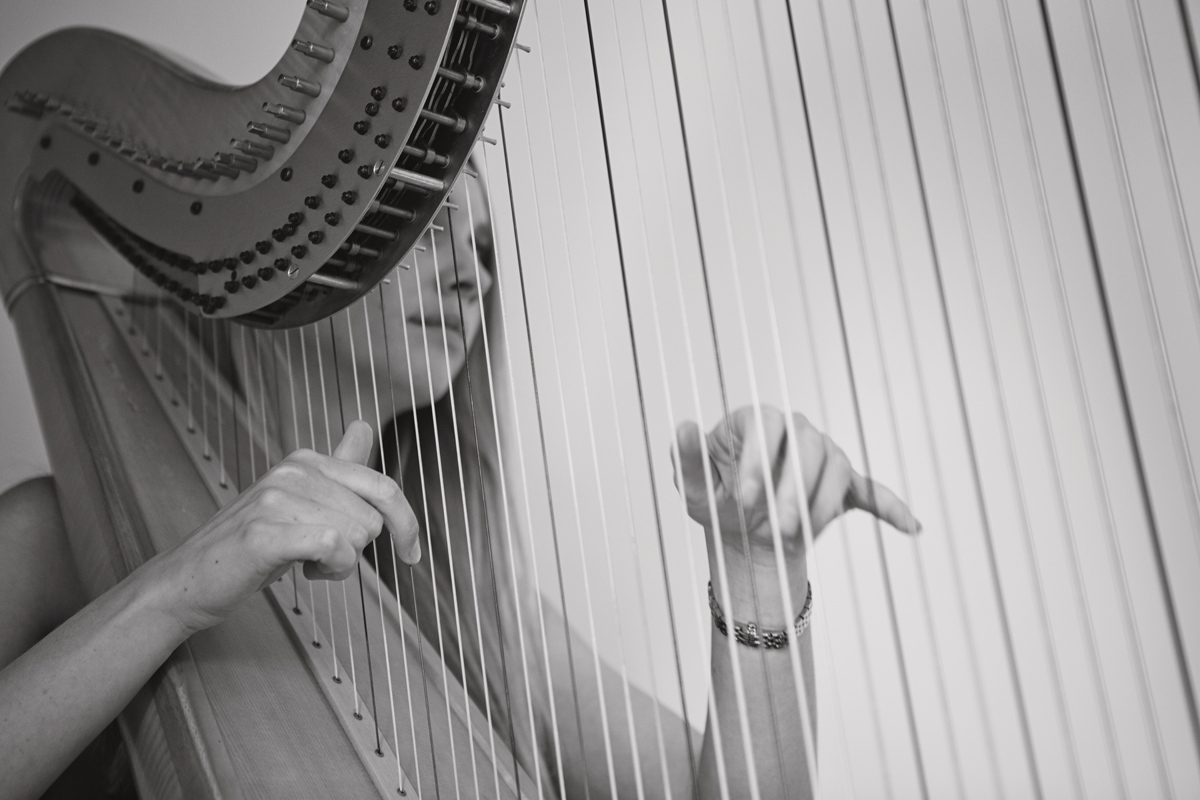 A close up of a harpists hands as she plays the strings at a wedding ceremony