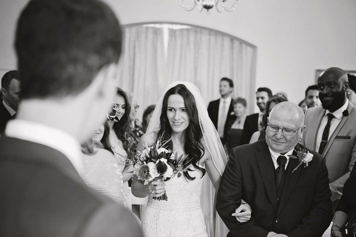 A shot from over the Groom's shoulder as the bride walks down the aisle with her father at a wedding