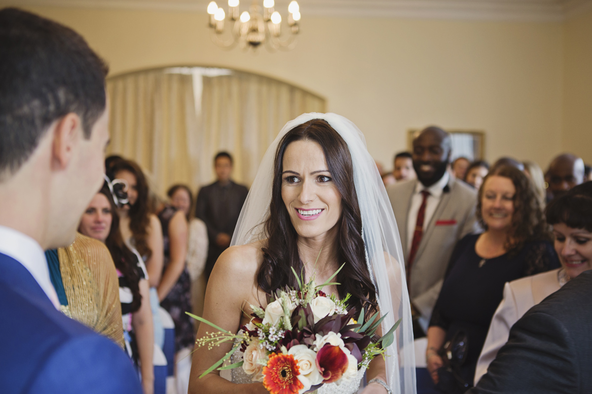 A bride smiles at her husband to be at her wedding ceremony