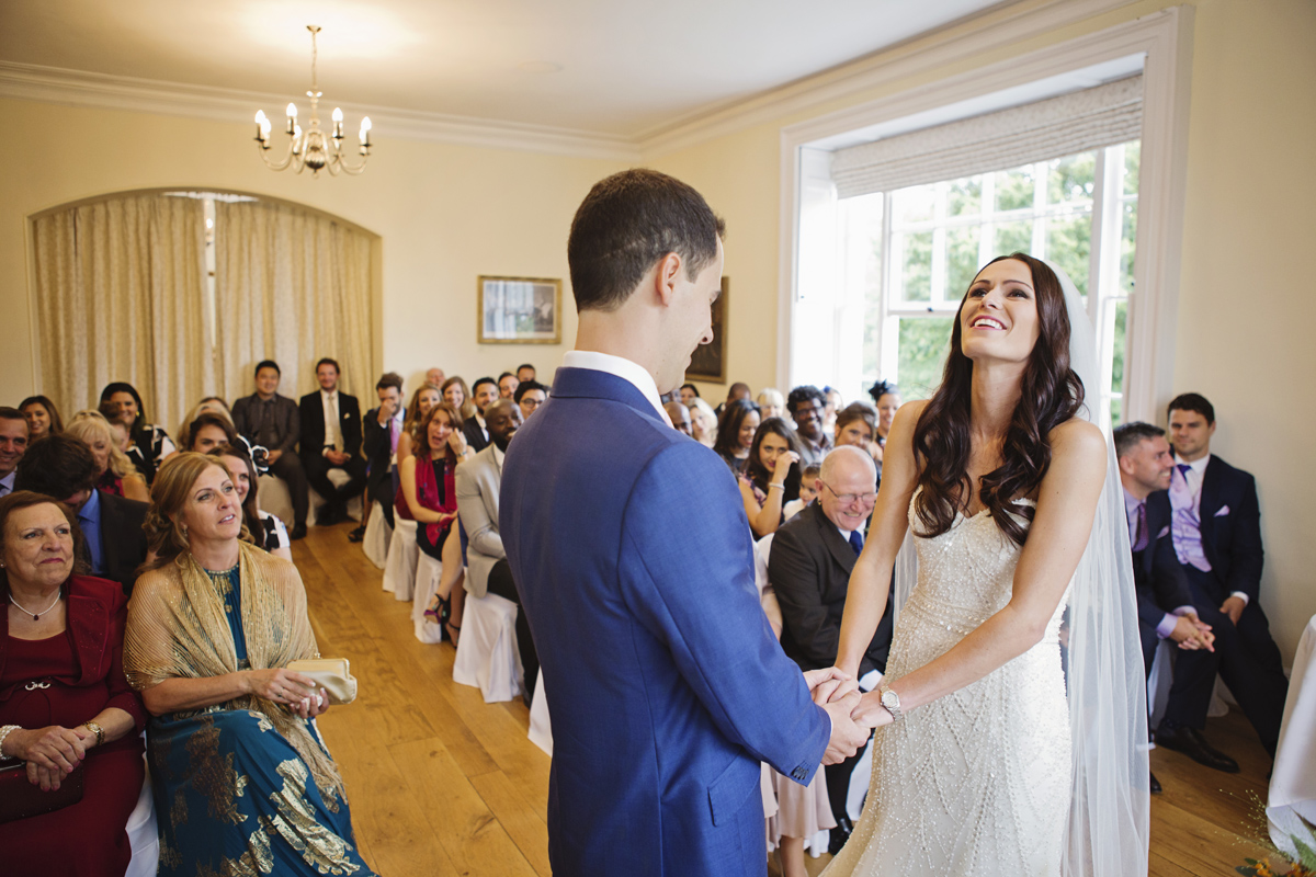 A wedding couple hold hands and laugh during their ceremony at Pembroke Lodge
