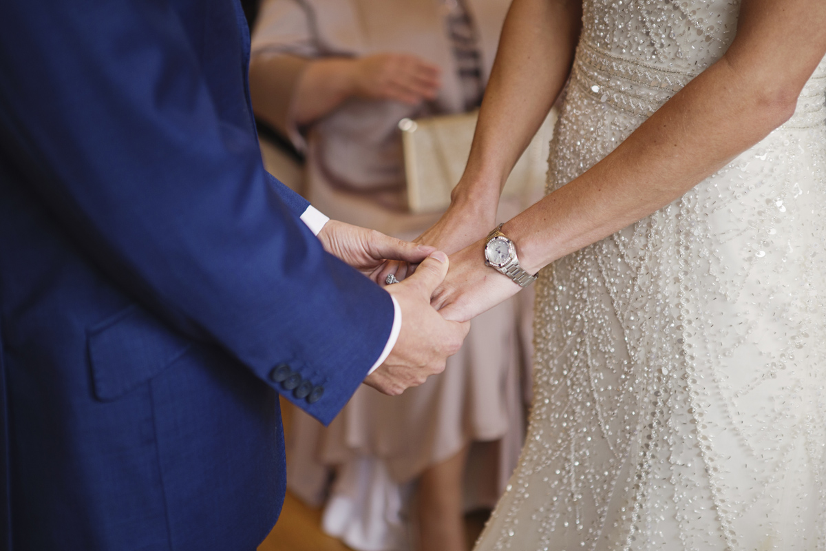 A close up shot of a wedding couple holding hands during their ceremony