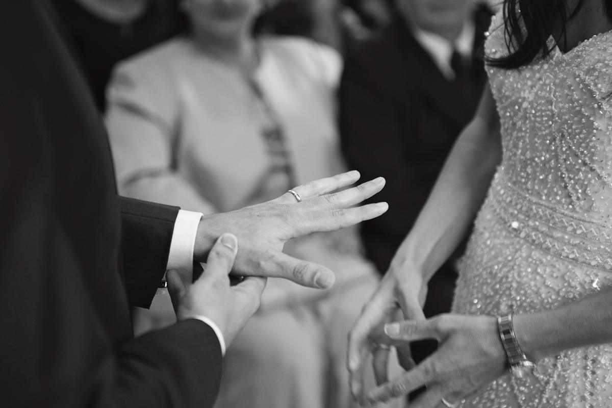A close up of a groom's hand as he admires his wedding ring during the ceremony