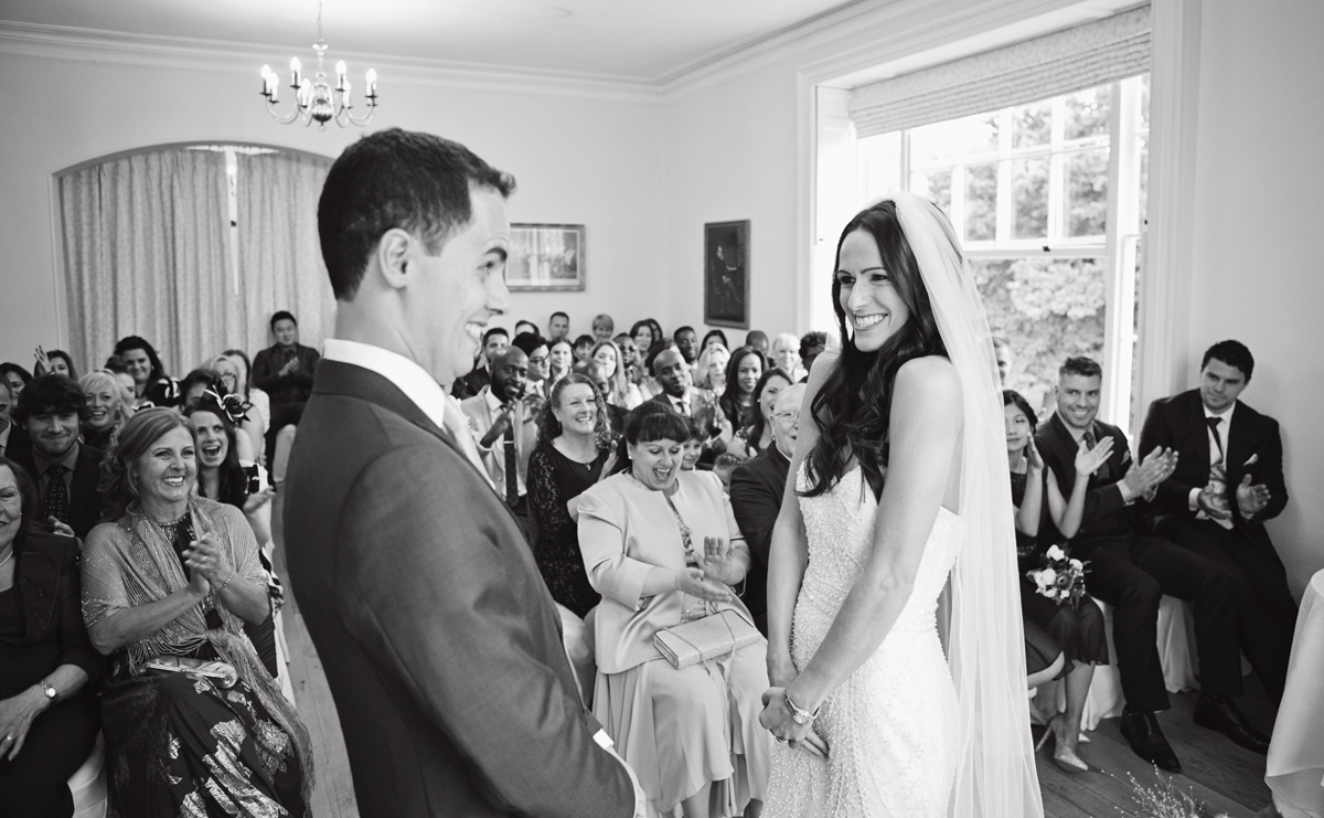 A bride & groom smile coyly at each other during their wedding ceremony as their guests clap their hands