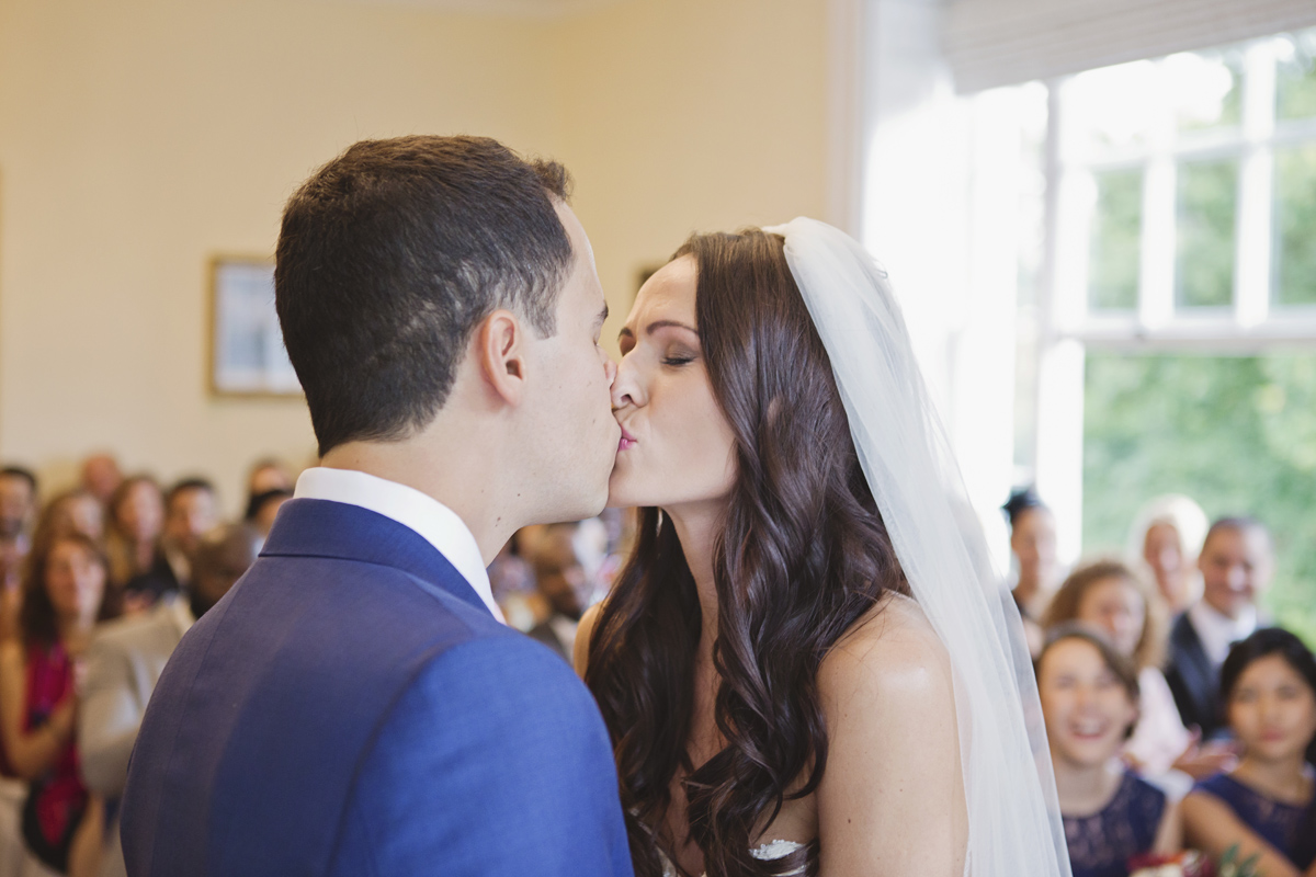 Newlyweds kiss at the end of their wedding ceremony at Pembroke Lodge