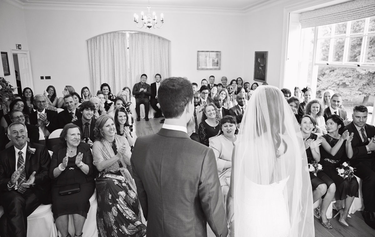 Newlyweds face their guests as they clap at the end of their wedding ceremony at Pembroke Lodge