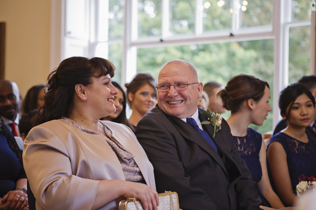 The bride's parents smile at each other during her wedding ceremony