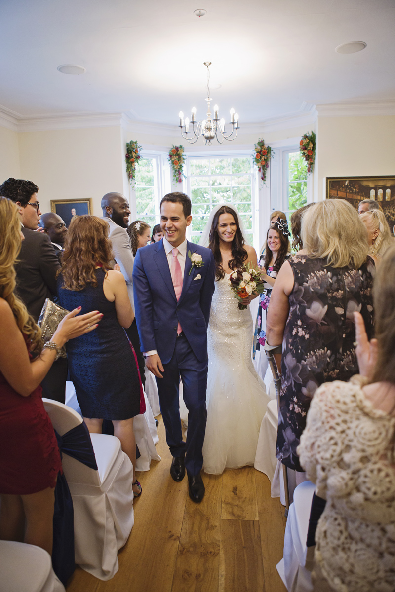 A newlywed couple walk down the aisle at their wedding at Pembroke Lodge in Richmond