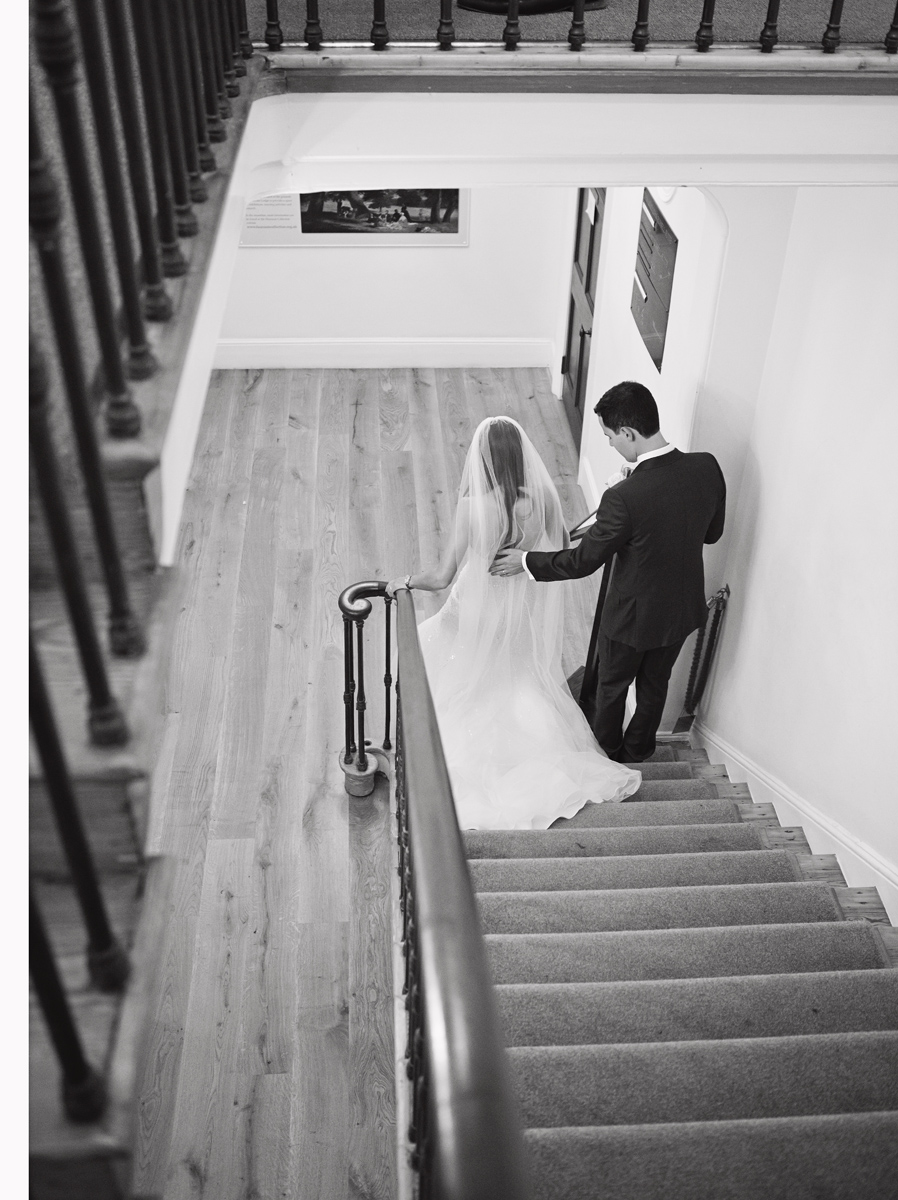 A Groom helps his bride down the stairs at their wedding in Pembroke Lodge, Richmond