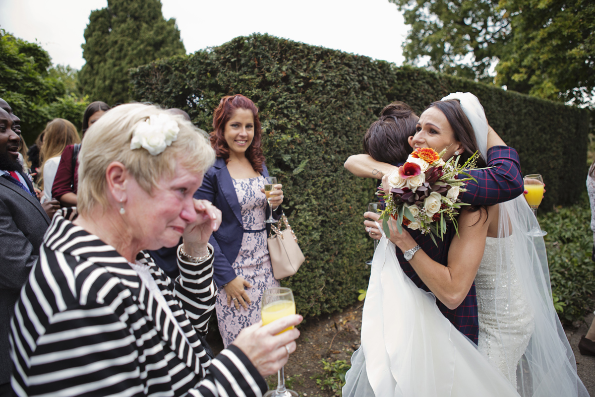 A guest cries with happiness as a bride hugs a fellow guest on her wedding day in the grounds of Pembroke Lodge in Richmond