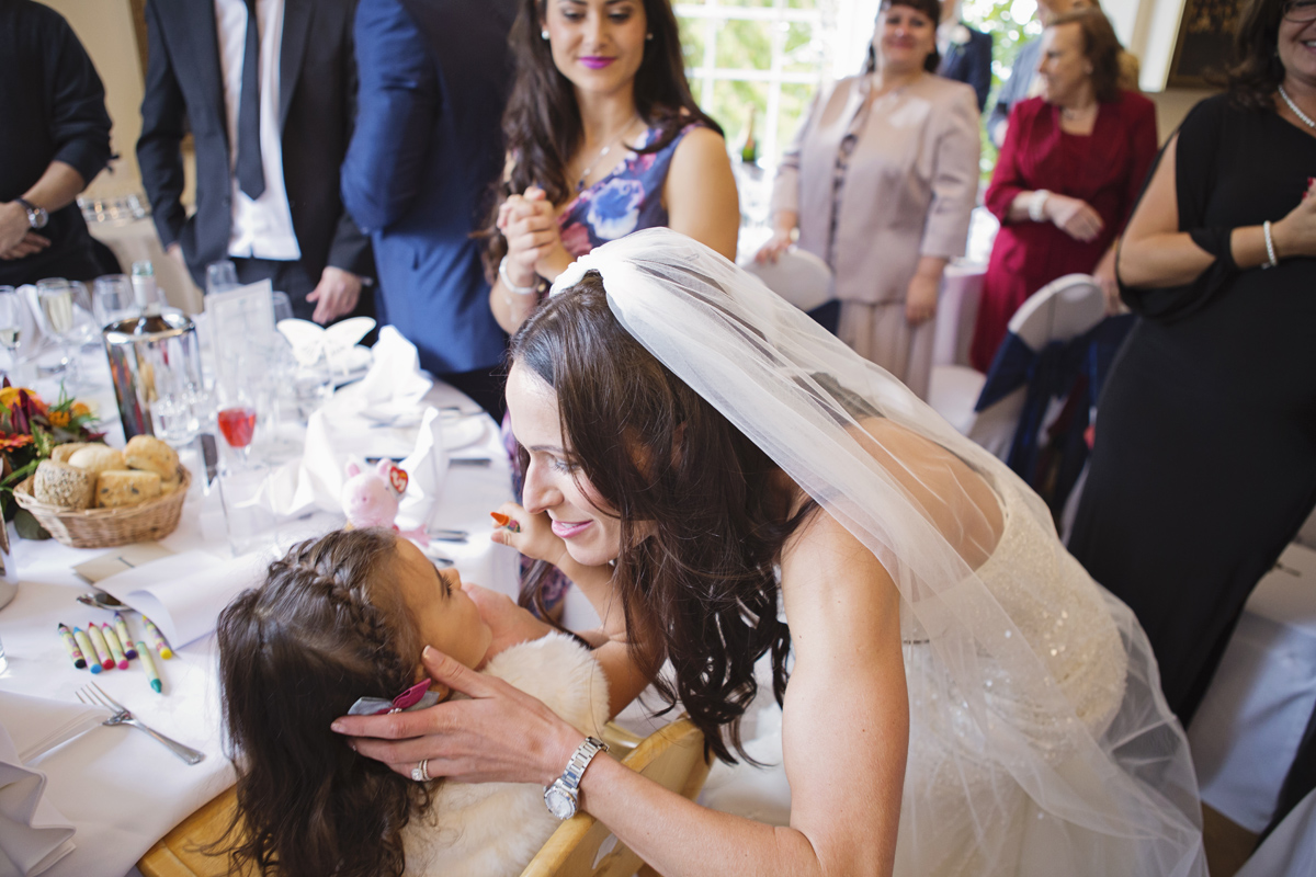 A bride hugs a little girl at her wedding breakfast at Pembroke Lodge