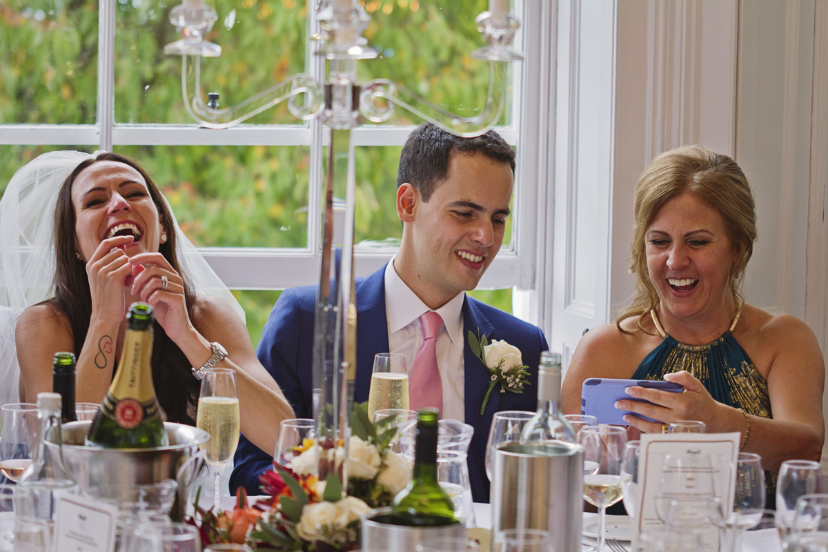 A bride & groom laugh as they look at pictures with the groom's mother at the table during their wedding breakfast