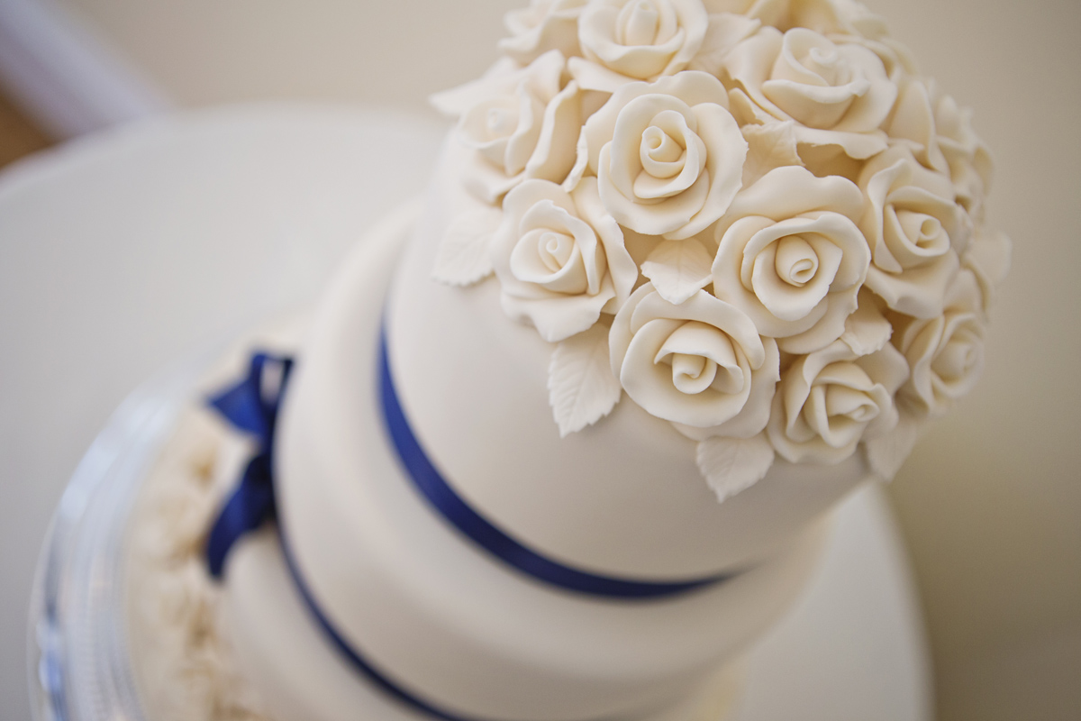 A close up of a white wedding cake with icing shaped like flowers and a blue ribbon