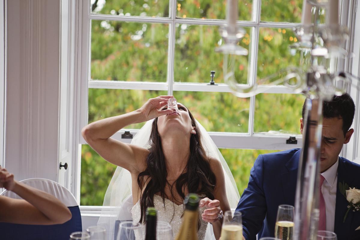 A bride & groom drink shots during their wedding breakfast