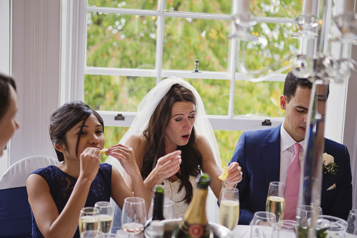 A bride pulls a face after drinking a shot of Tequila at her wedding breakfast at Pembroke Lodge