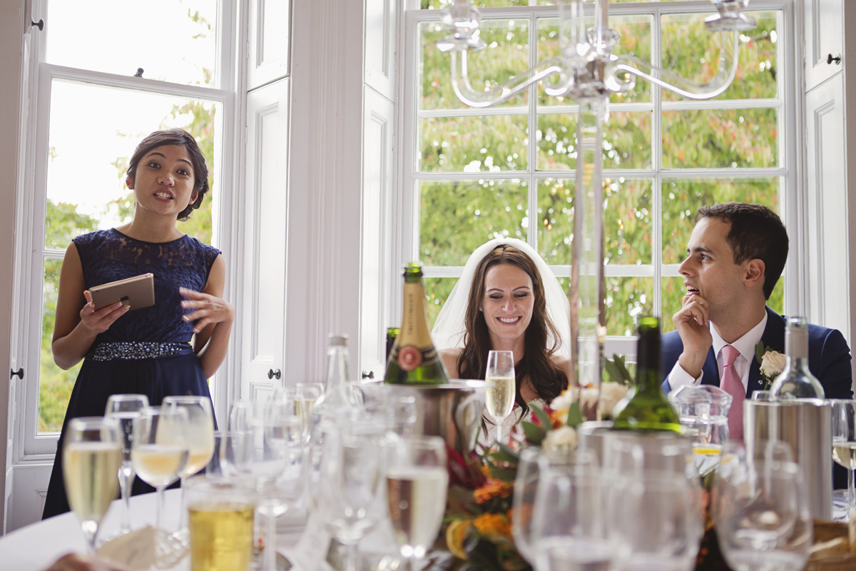 A bridesmaid gives a speech at the wedding breakfast as the bride & groom look on smiling