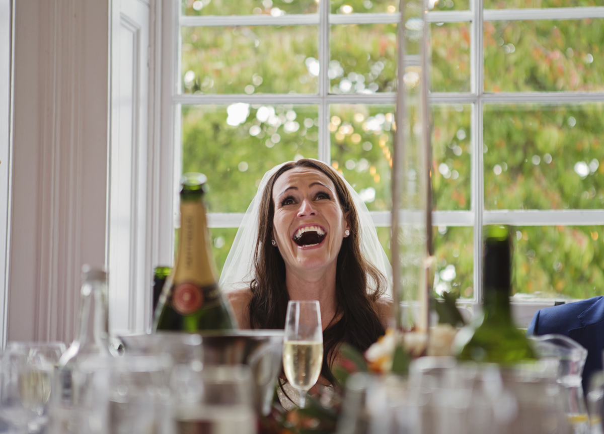 A bride bursts out laughing during the speeches at her wedding breakfast