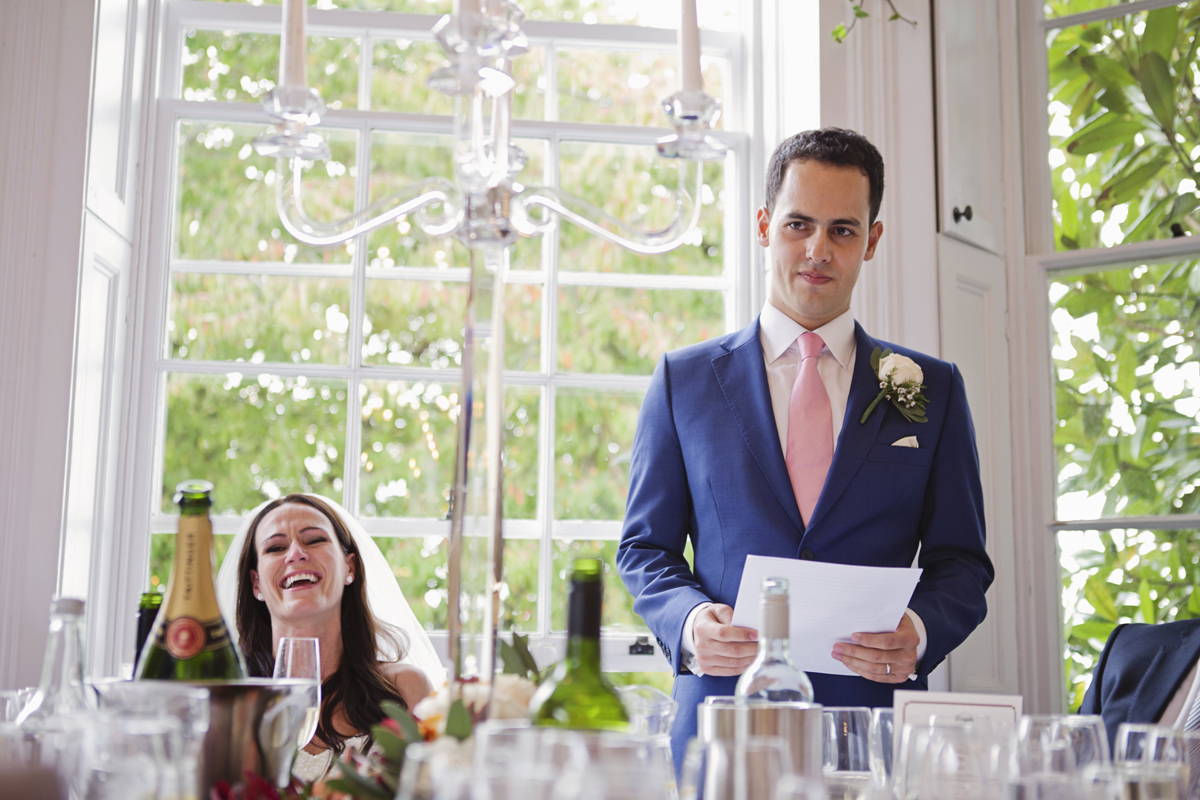 A bride laughs as her husband gives his wedding speech