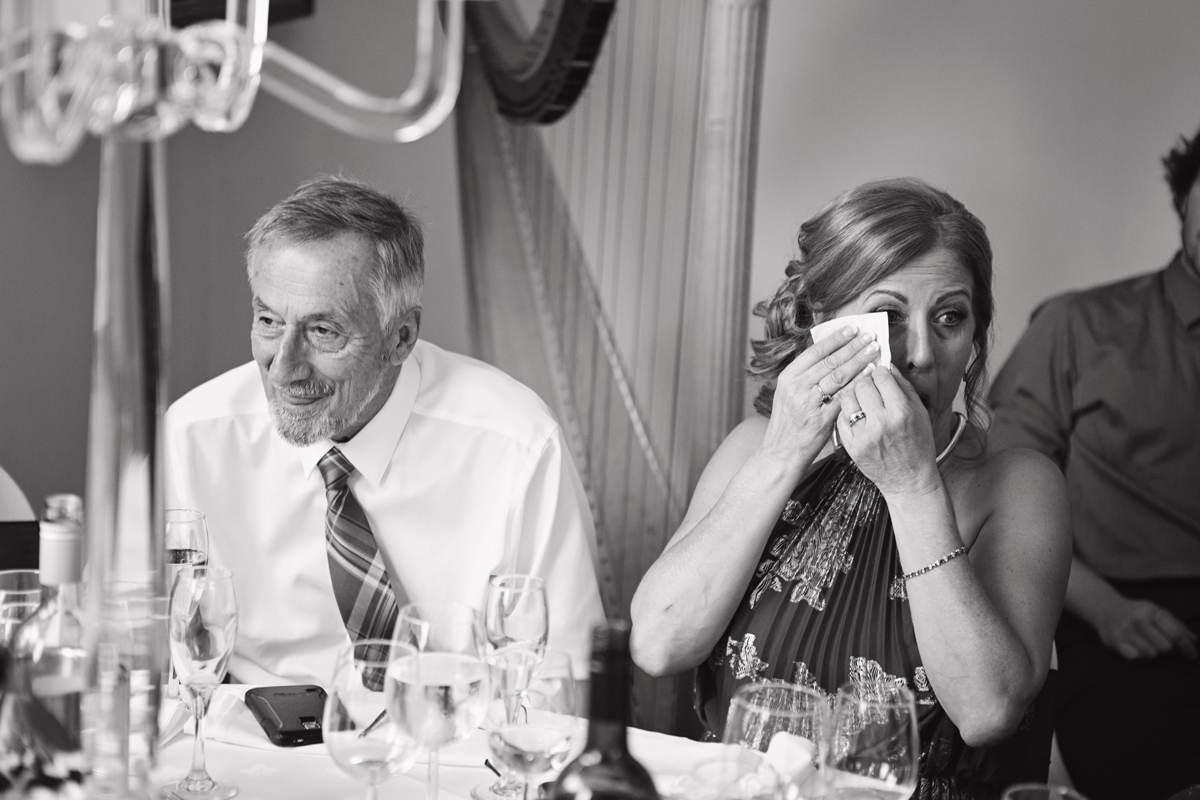 The Groom's mother wipes away tears during her son's speech as his dad smiles