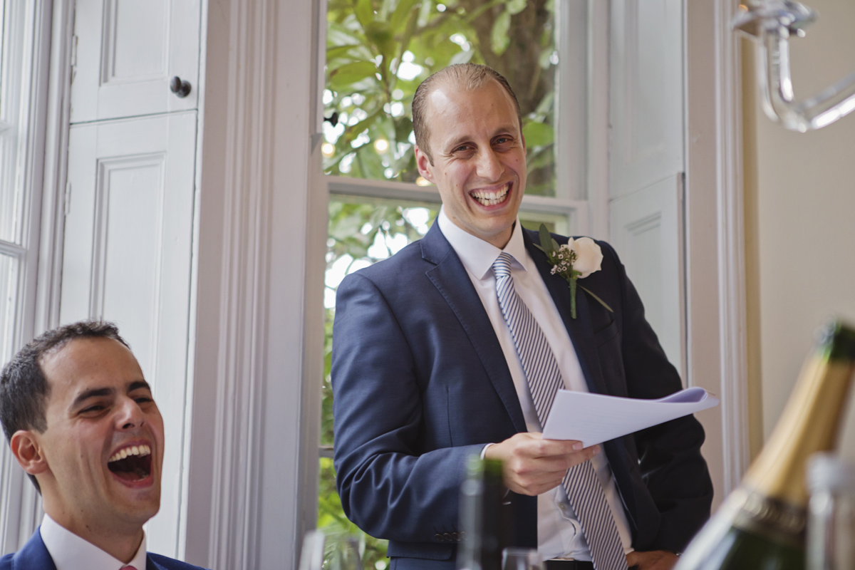 The Groom and Best Man laugh during his speech at a wedding in Pembroke Lodge, Richmond
