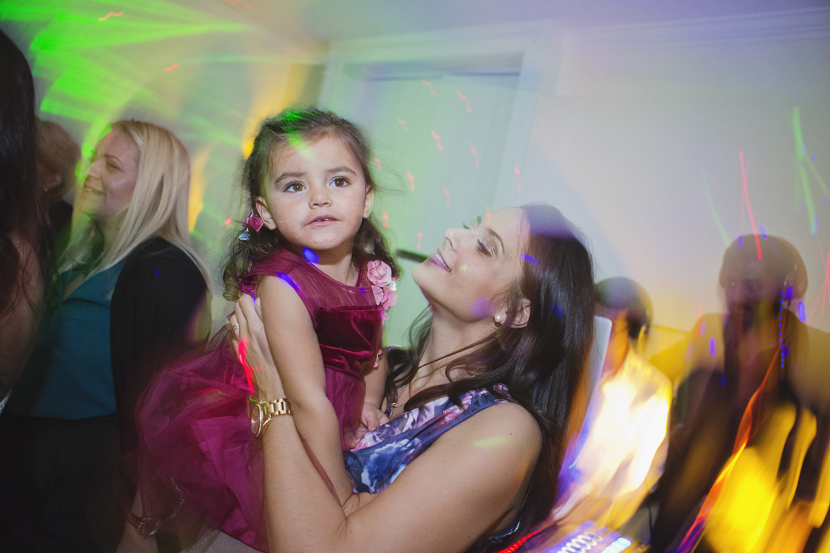 A wedding guest holds up her little girl while dancing at a wedding reception with coloured light trails swirling around them