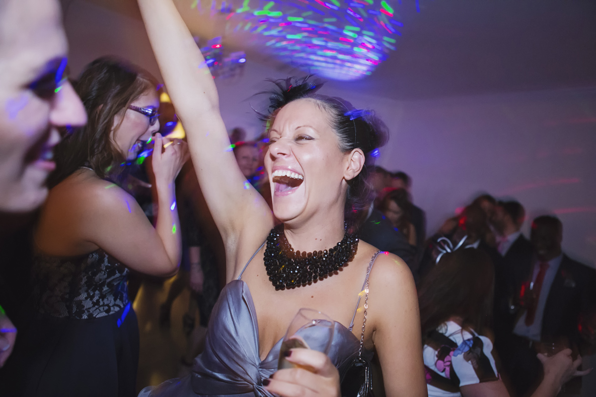 A wedding guest raise her hand and laughs while dancing at a reception