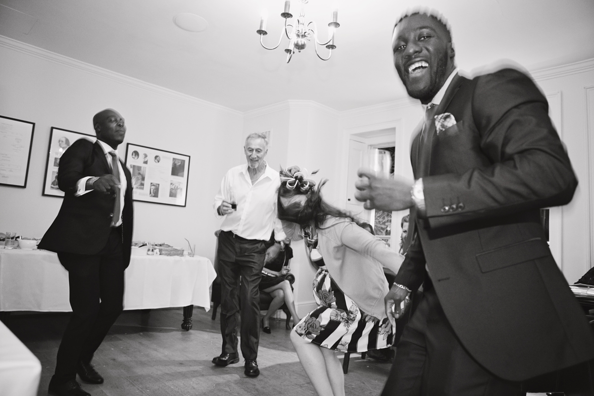 A black & white shot of wedding guests dancing at a reception