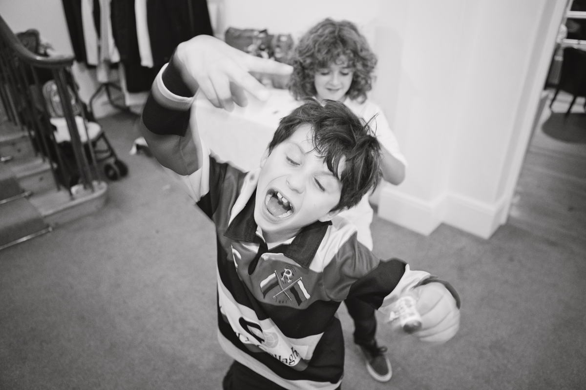 Two boys dance towards the camera during a wedding reception