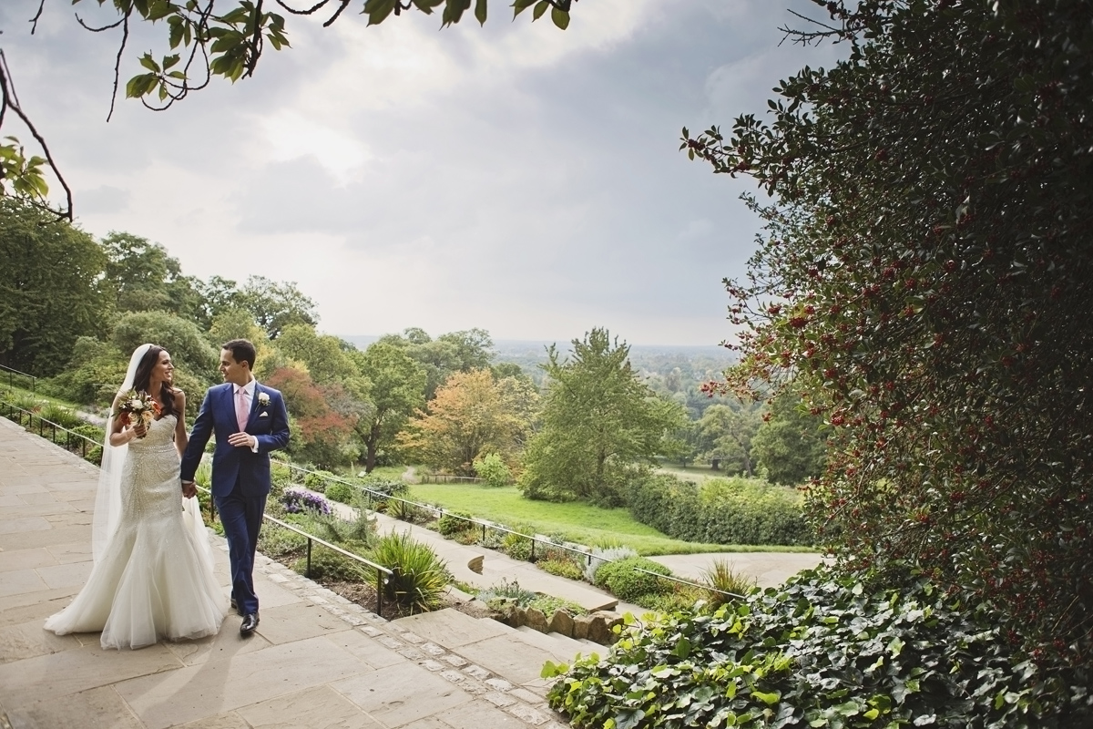 A bride & groom stroll through the grounds of Pembroke Lodge with views of Richmond Park in the background