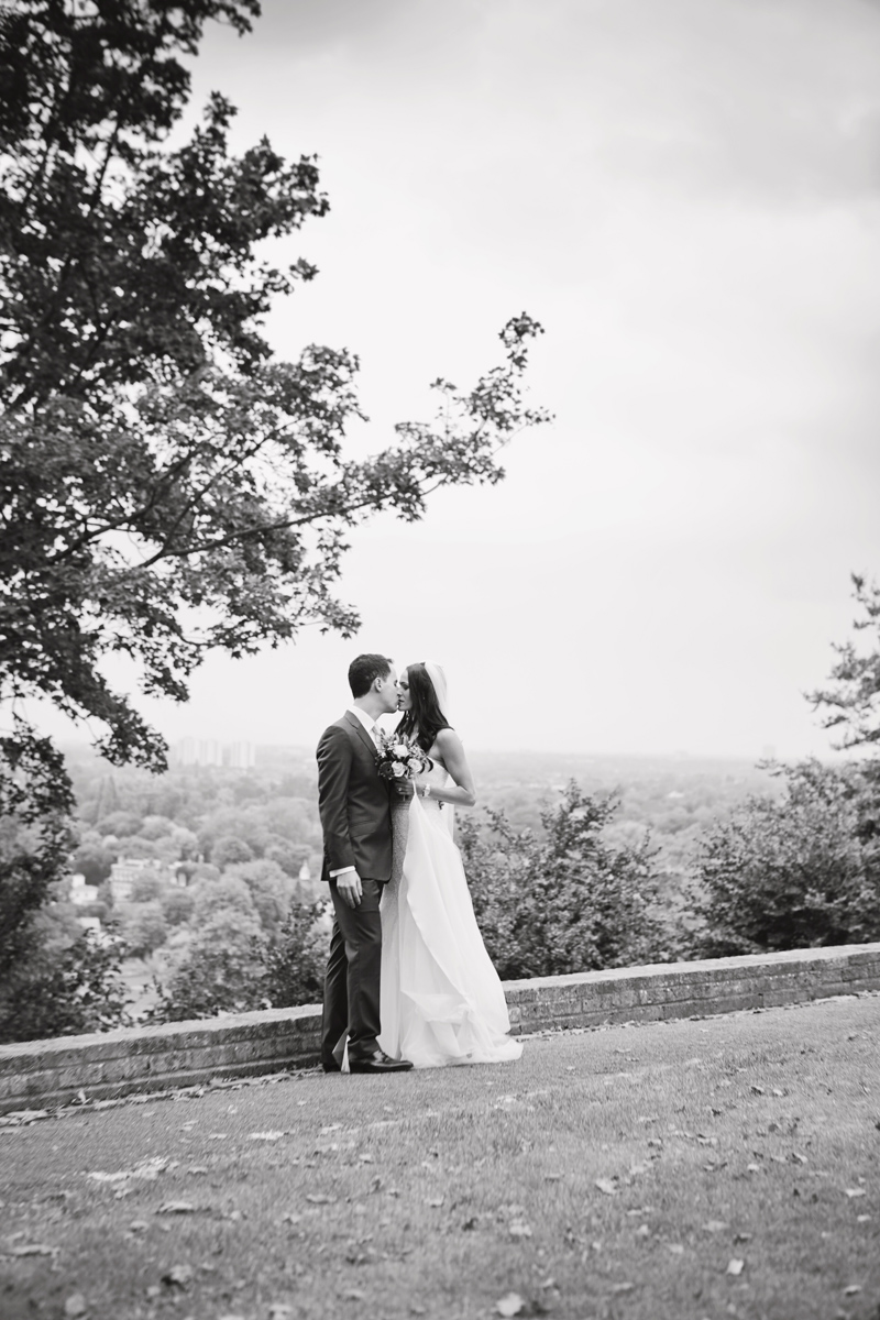 A newlywed couple kiss with views of the Thames Valley behind them in Richmond Park