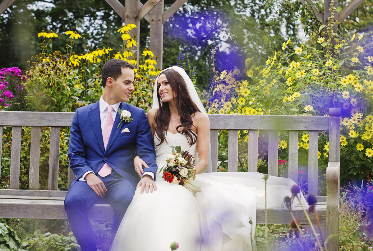 A bride & groom sit chatting on a park bench surrounded by purple & yellow flowers in Richmond Park