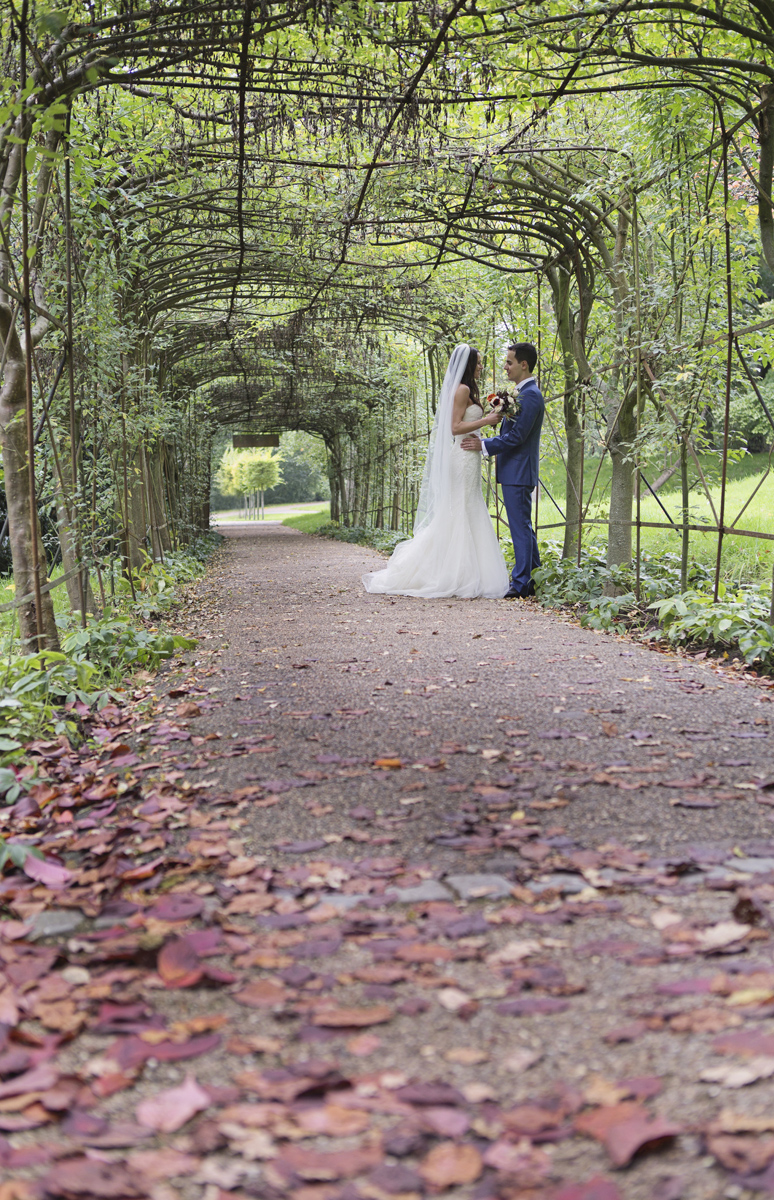 A bride & groom face each other underneath a long covered walkway of vines in Richmond Park