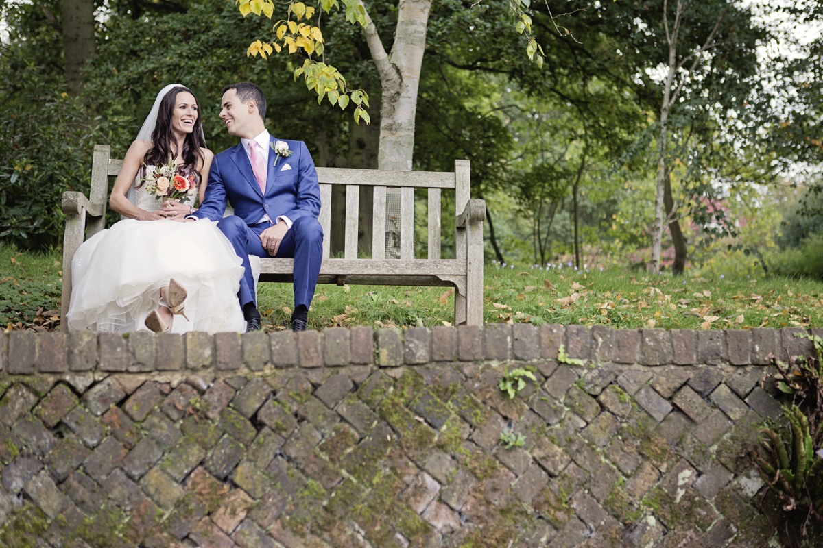A bride & groom laugh together as they sit on a bench behind a small wall in Richmond Park