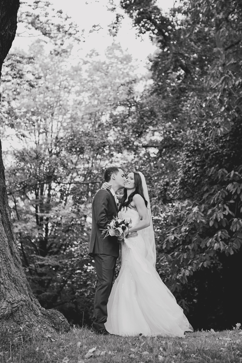 A groom kisses his bride while standing in a woodland park