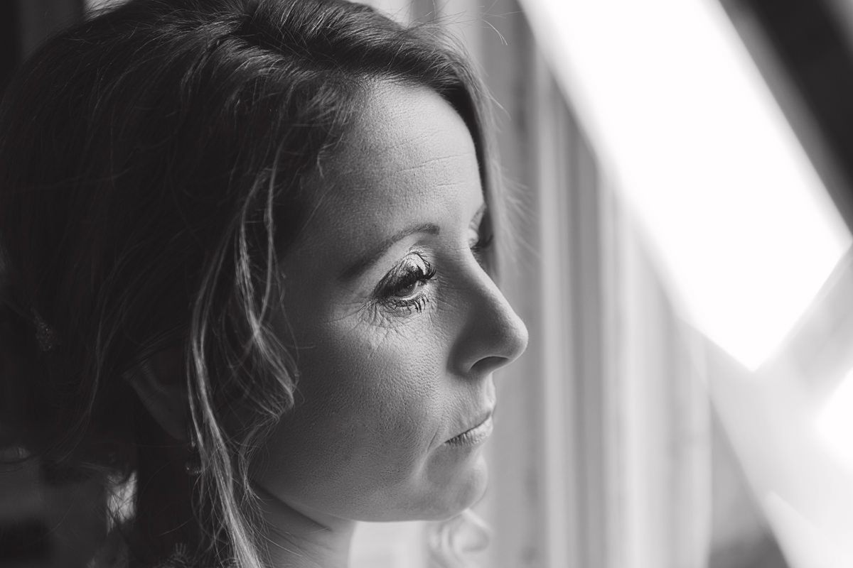 A close up black & white shot of a bride looking pensively out of a a window