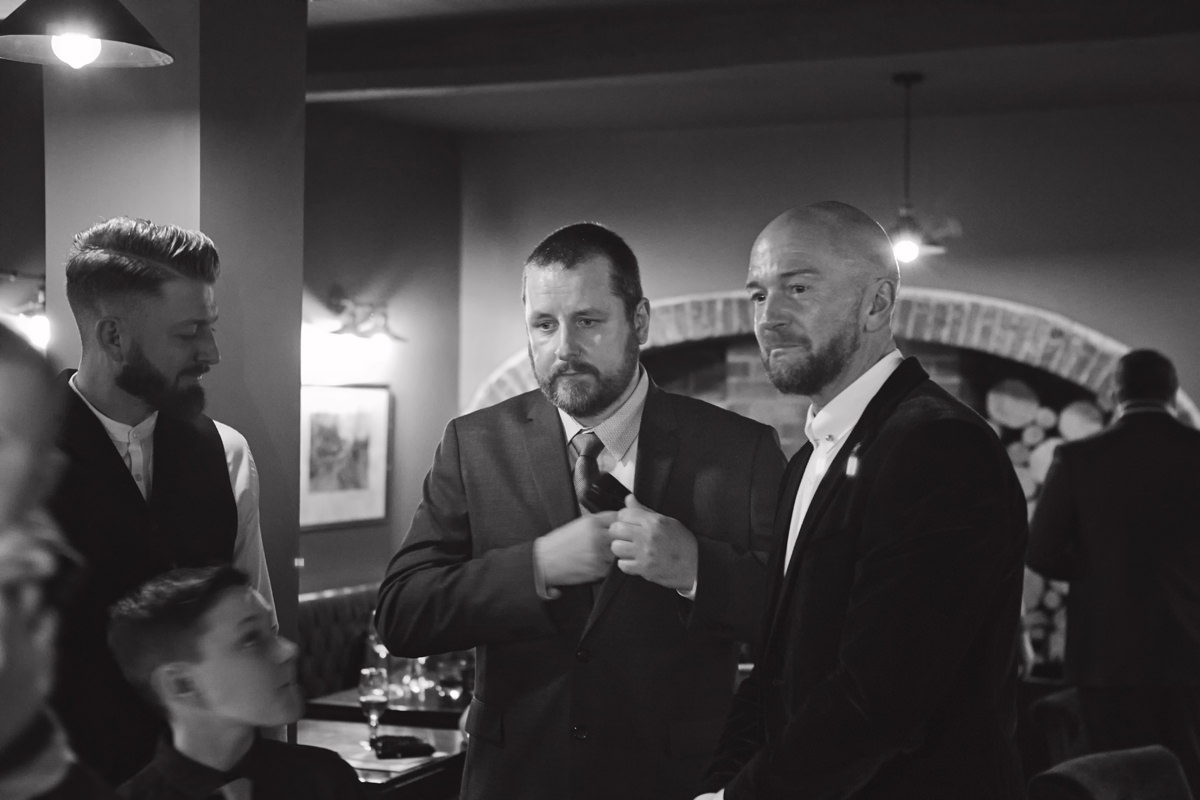 A groom waits with his guests in a pub before his wedding ceremony