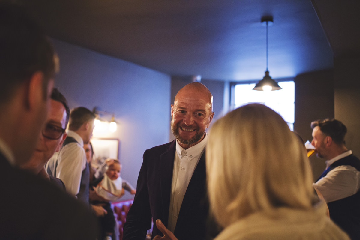 A groom smiles at a guest as they chat in a pub before his wedding