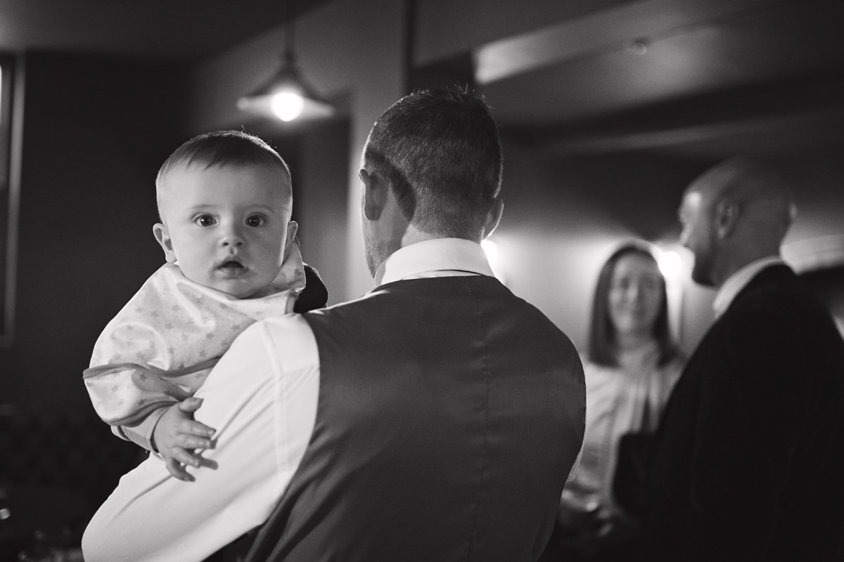 A black & white shot of a baby looking over his Dad's shoulder at the camera