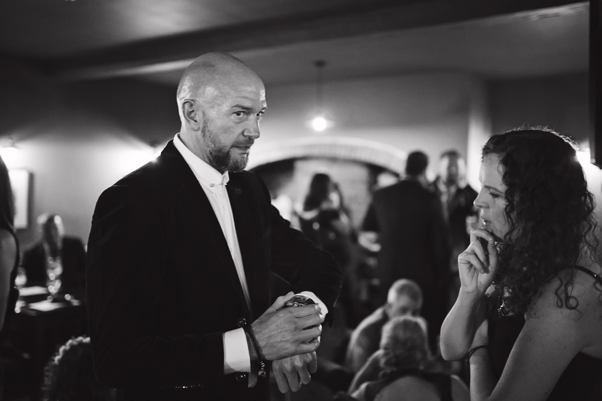 A groom checks his watch while talking to a guest in a pub