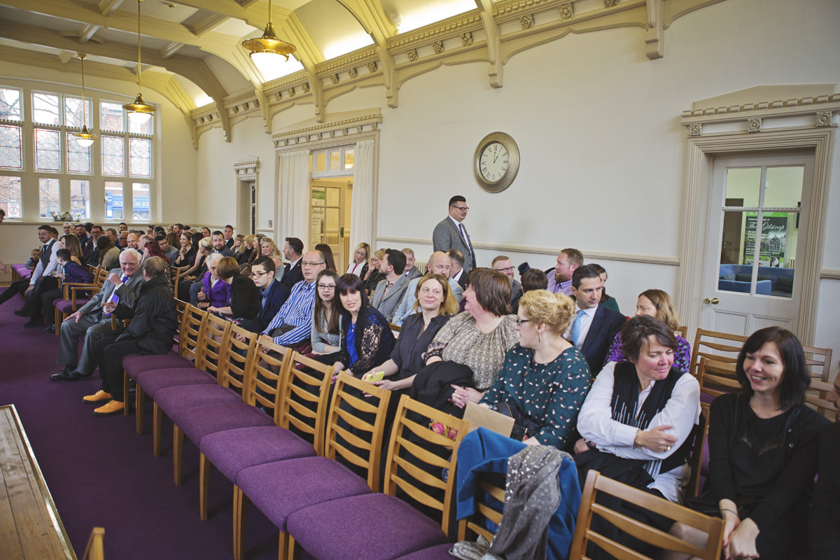A wide shot of a registry office as the guests tale their seats for a wedding ceremony