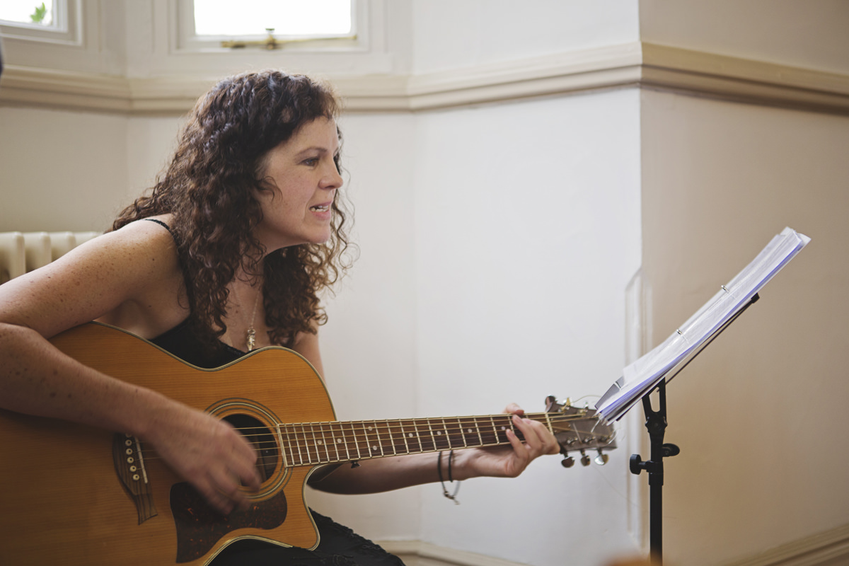 A woman plays an acoustic guitar at a wedding ceremony
