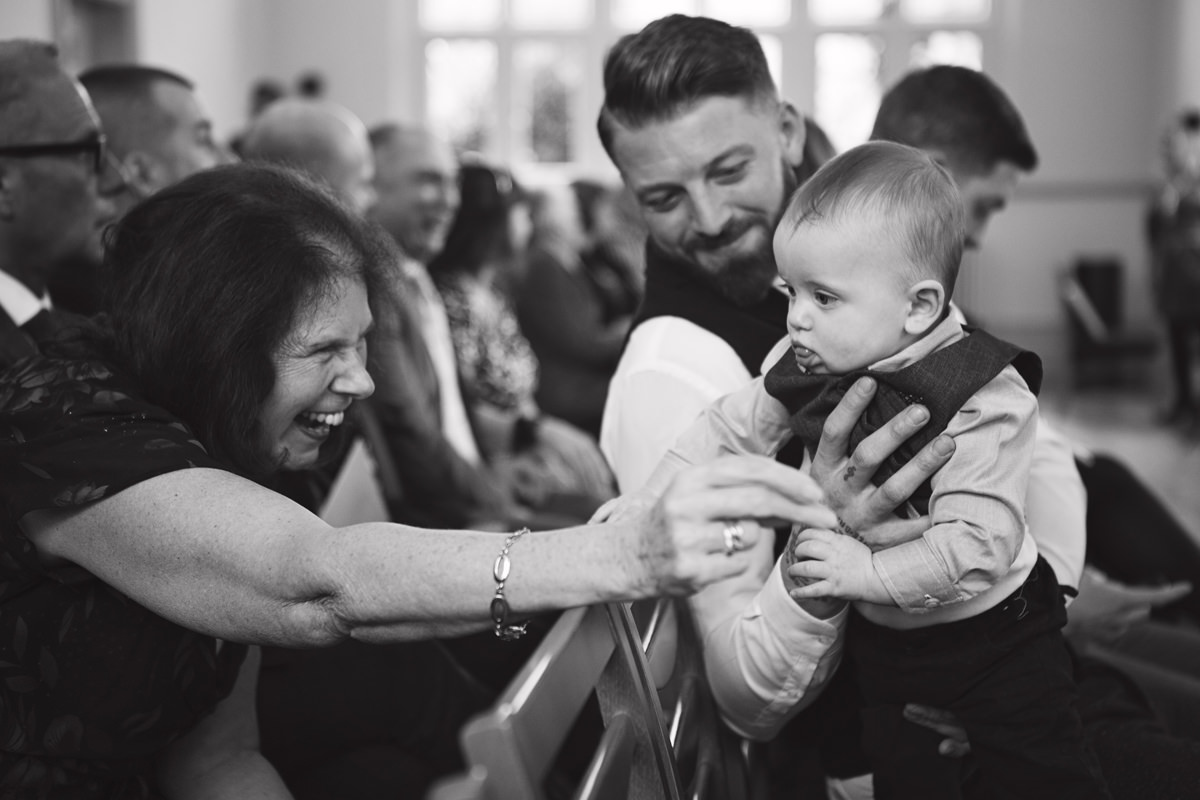 A toddler is being entertained by his grandmother while awaiting the start of a wedding ceremony