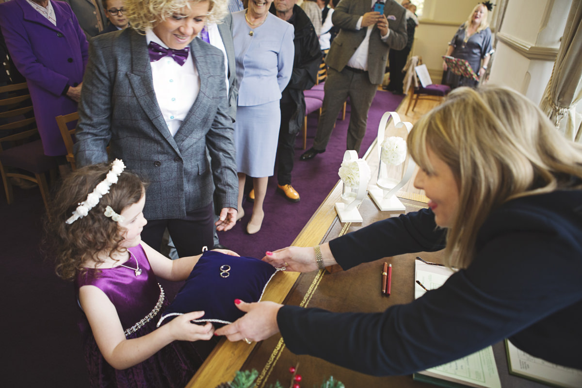 A little girl acts as ring bearer at a wedding and passes them to the officiant during the ceremony