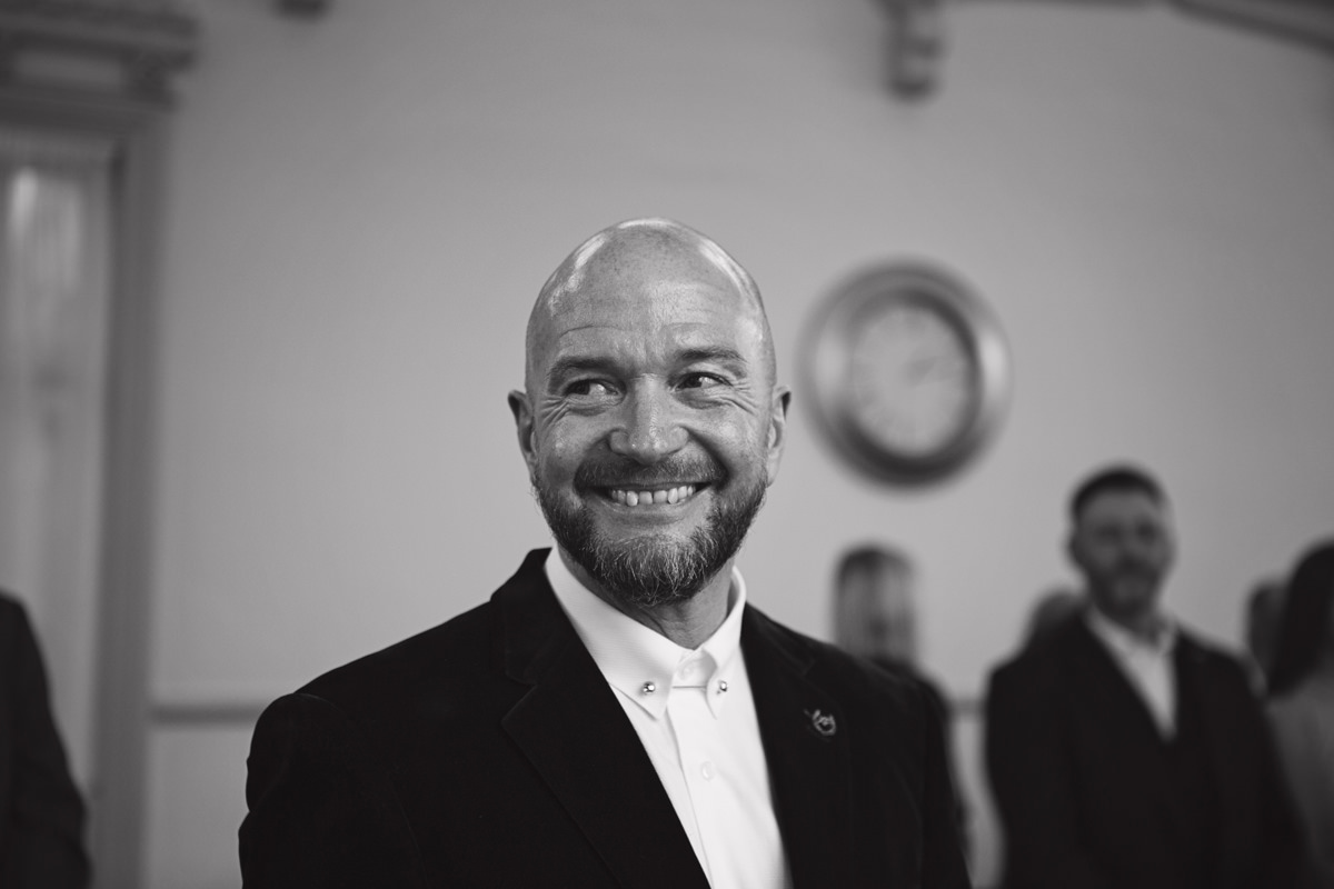 A black & white close up of a groom smiling at his wedding ceremony