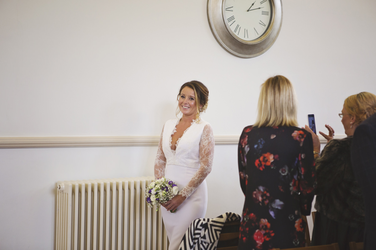 A bride walks alone down the aisle at a registry office ceremony as her guests take pictures