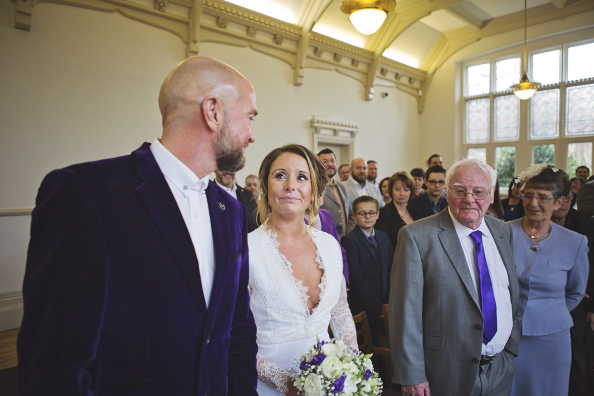 A bride looks at her groom with her parents in the background during her wedding ceremony