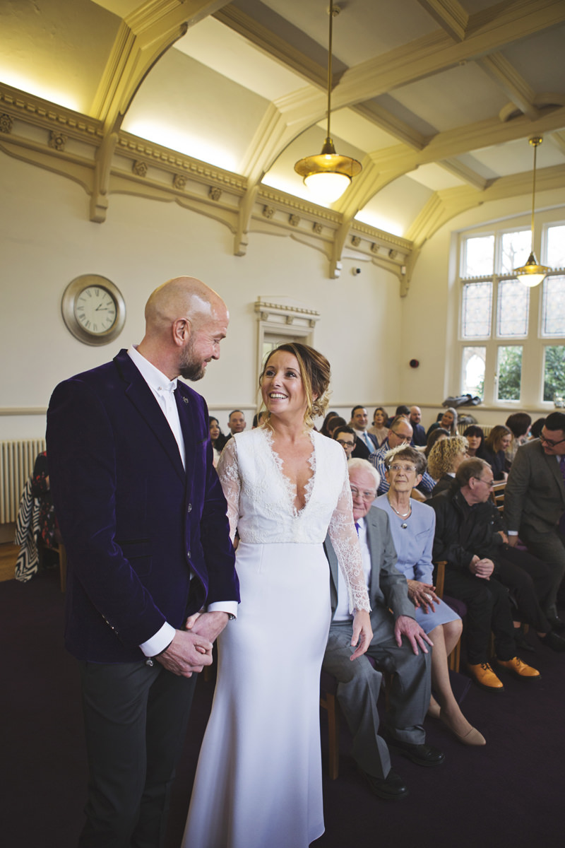 A wedding couple smile at each other surrounded by their guests at their wedding ceremony