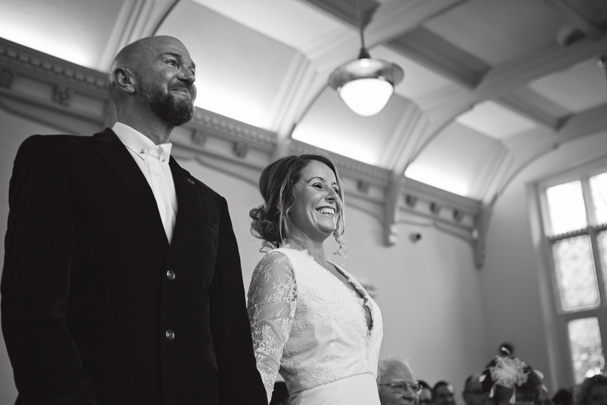 A low angle shot looking up to a wedding couple standing at the alter smiling
