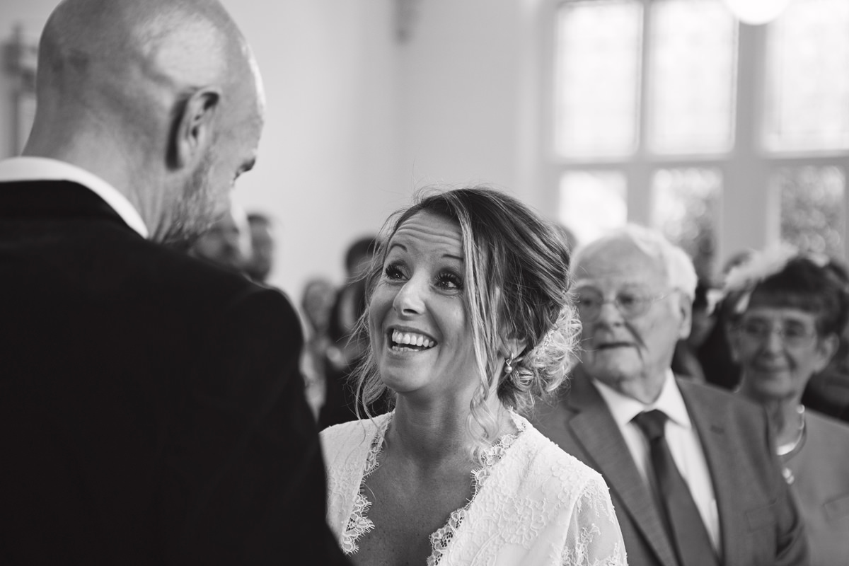 A bride laughs while facing her groom during the exchange of vows