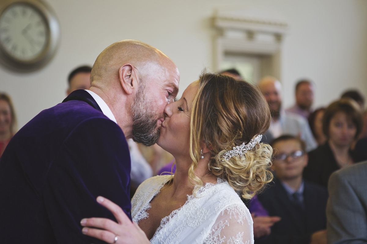 A bride & groom share a kiss at the end of their wedding ceremony